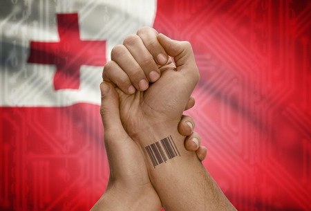 dark skinned: Barcode ID number tattoo on wrist of dark skinned person and national flag on background - Tonga Stock Photo