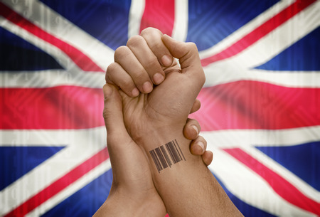 dark skinned: Barcode ID number tattoo on wrist of dark skinned person and national flag on background - United Kingdom Stock Photo