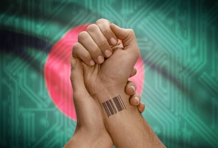 national flag bangladesh: Barcode ID number tattoo on wrist of dark skinned person and national flag on background - Bangladesh Stock Photo