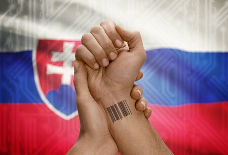 dark skinned: Barcode ID number tattoo on wrist of dark skinned person and national flag on background - Slovakia