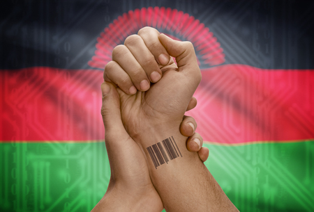 malawian flag: Barcode ID number tattoo on wrist of dark skinned person and national flag on background - Malawi