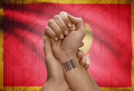 dark skinned: Barcode ID number tattoo on wrist of dark skinned person and national flag on background - Montenegro