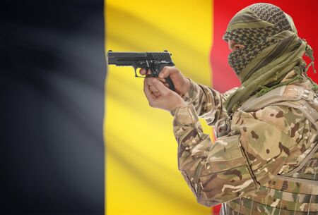 rebel flag: Male in muslim keffiyeh with gun in hand and national flag on background series - Belgium