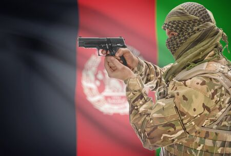 extremist: Male in muslim keffiyeh with gun in hand and national flag on background series - Afghanistan