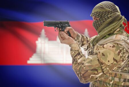 extremist: Male in muslim keffiyeh with gun in hand and national flag on background series - Cambodia