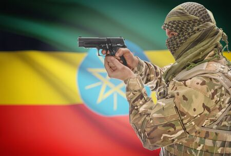 extremist: Male in muslim keffiyeh with gun in hand and national flag on background series - Ethiopia