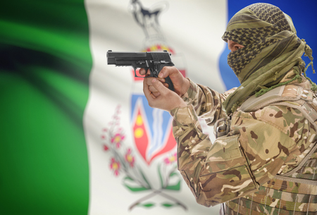 yukon: Male in muslim keffiyeh with gun in hand and Canadian province flag on background series - Yukon Stock Photo