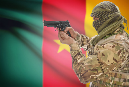 cameroonian: Male in muslim keffiyeh with gun in hand and national flag on background series - Cameroon Stock Photo