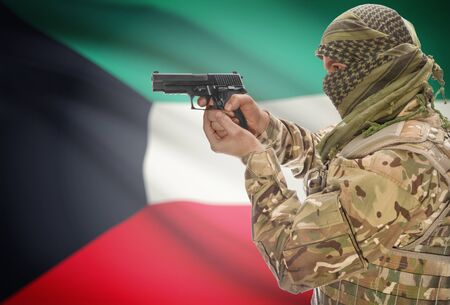 extremist: Male in muslim keffiyeh with gun in hand and national flag on background series - Kuwait