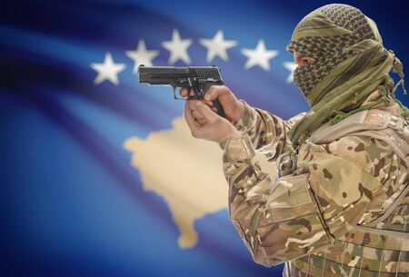 extremist: Male in muslim keffiyeh with gun in hand and national flag on background series - Kosovo Stock Photo