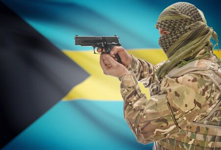 extremist: Male in muslim keffiyeh with gun in hand and national flag on background series - Bahamas