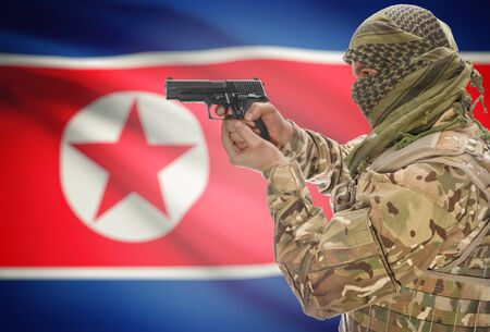 extremist: Male in muslim keffiyeh with gun in hand and national flag on background series - North Korea Stock Photo