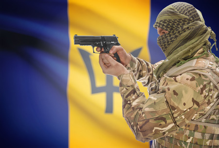 Male in muslim keffiyeh with gun in hand and national flag on background series - Barbados Stock Photo