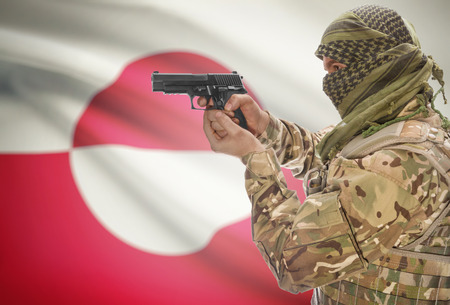 greenlandic: Male in muslim keffiyeh with gun in hand and national flag on background series - Greenland Stock Photo