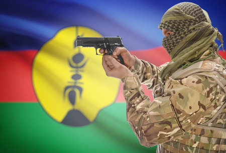 new caledonia: Male in muslim keffiyeh with gun in hand and national flag on background series - New Caledonia