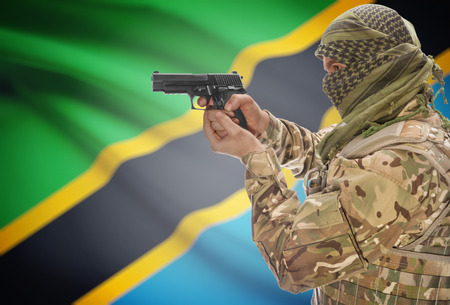 extremist: Male in muslim keffiyeh with gun in hand and national flag on background series - Tanzania