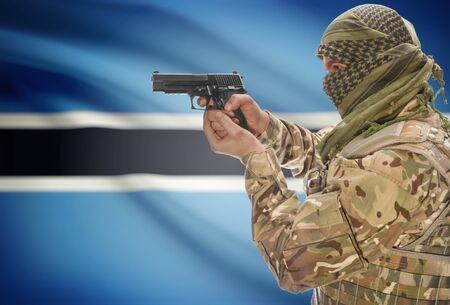 botswanan: Male in muslim keffiyeh with gun in hand and national flag on background series - Botswana Stock Photo