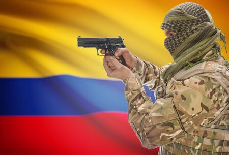 extremist: Male in muslim keffiyeh with gun in hand and national flag on background series - Colombia