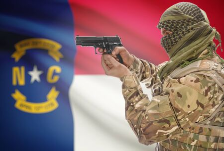extremist: Male in muslim keffiyeh with gun in hand and flag on background series - North Carolina Stock Photo
