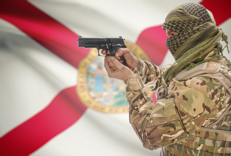 floridian: Male in muslim keffiyeh with gun in hand and flag on background series - Florida Stock Photo