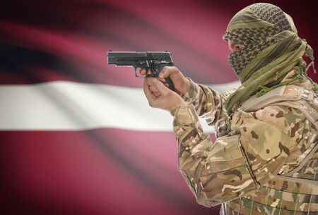 extremist: Male in muslim keffiyeh with gun in hand and national flag on background series - Latvia