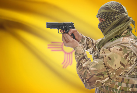 extremist: Male in muslim keffiyeh with gun in hand and flag on background series - New Mexico