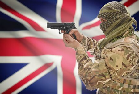extremist: Male in muslim keffiyeh with gun in hand and national flag on background series - United Kingdom Stock Photo