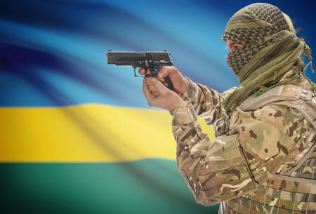 extremist: Male in muslim keffiyeh with gun in hand and national flag on background series - Rwanda Stock Photo