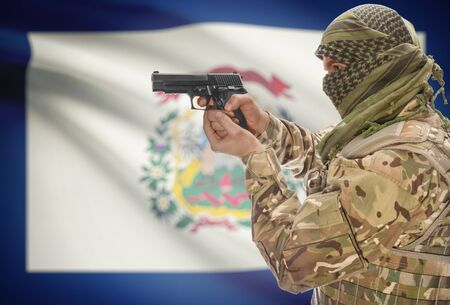 extremist: Male in muslim keffiyeh with gun in hand and flag on background series - West Virginia Stock Photo