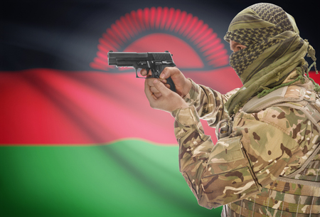 malawian flag: Male in muslim keffiyeh with gun in hand and national flag on background series - Malawi Stock Photo