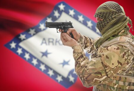 extremist: Male in muslim keffiyeh with gun in hand and flag on background series - Arkansas