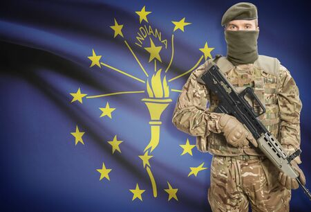 peacemaker: Soldier holding machine gun with USA state flag on background - Indiana Stock Photo