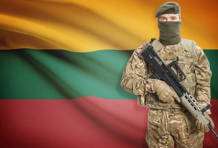 peacemaker: Soldier holding machine gun with national flag on background - Lithuania