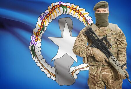 mariana: Soldier holding machine gun with national flag on background - Northern Mariana Islands