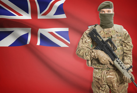 canadian military: Soldier holding machine gun with Canadian province flag on background - Manitoba Stock Photo