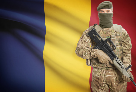 peacemaker: Soldier holding machine gun with national flag on background - Romania