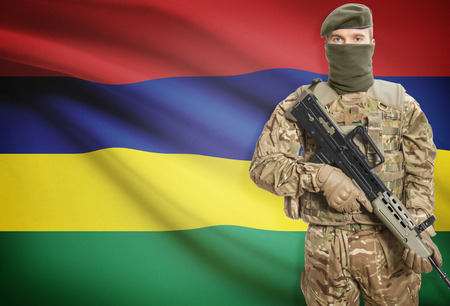 peacemaker: Soldier holding machine gun with national flag on background - Mauritius