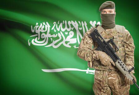 Soldier holding machine gun with national flag on background - Saudi Arabia Stock Photo