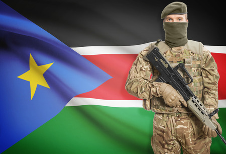 south sudan: Soldier holding machine gun with national flag on background - South Sudan Stock Photo