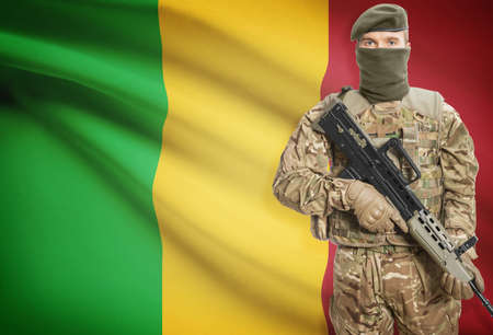 peacemaker: Soldier holding machine gun with national flag on background - Mali
