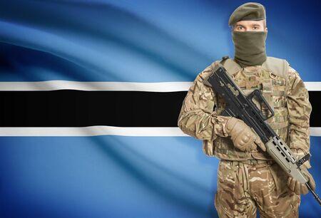 botswanan: Soldier holding machine gun with national flag on background - Botswana