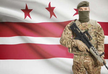 district columbia: Soldier holding machine gun with USA state flag on background - District of Columbia