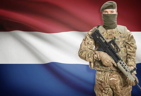 peacemaker: Soldier holding machine gun with national flag on background - Netherlands