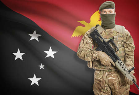 papua new guinea: Soldier holding machine gun with national flag on background - Papua New Guinea
