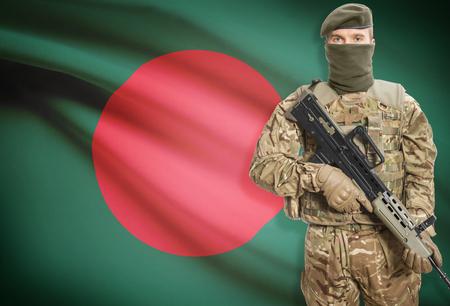 national flag bangladesh: Soldier holding machine gun with national flag on background - Bangladesh Stock Photo