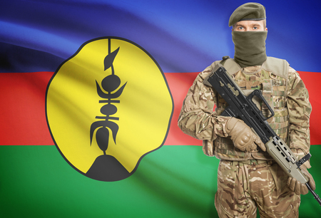 new caledonia: Soldier holding machine gun with national flag on background - New Caledonia Stock Photo