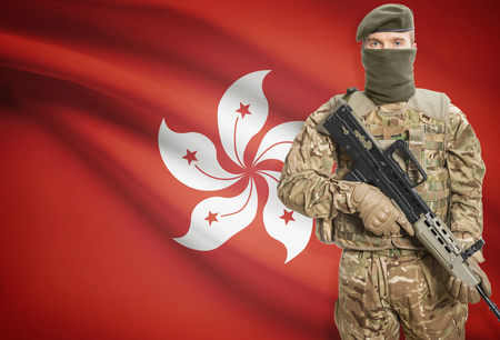 peacemaker: Soldier holding machine gun with national flag on background - Hong Kong Stock Photo
