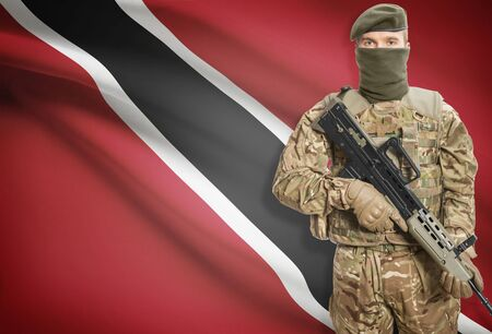 national flag trinidad and tobago: Soldier holding machine gun with national flag on background - Trinidad and Tobago