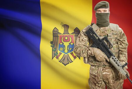 moldovan: Soldier holding machine gun with national flag on background - Moldova