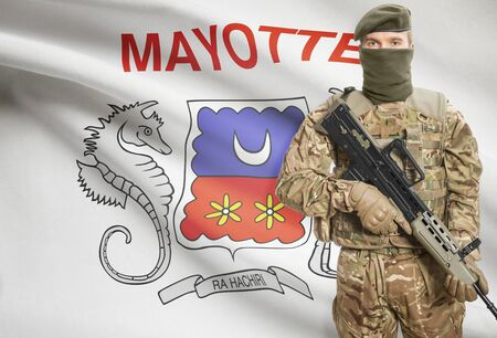 mayotte: Soldier holding machine gun with national flag on background - Mayotte Stock Photo